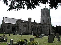 Stone building with prominent square tower. In the foreground are gravestones.