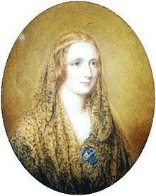 Oval portrait of a woman wearing a shawl and a thin circlet around her head. It is painted on a flax coloured background.
