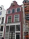 foto van Huis met geverfde klokgevel, door rollaag en natuurstenen halfronde top afgesloten