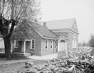 A three-quarters view of a brick church in a black-and-white photo. A barren tree is to the left and a pile of rubble lies to the right.