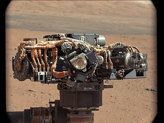 """Mars rover - Curiosity's (MSL) rover """"hand"""" featuring a suite of instruments on a rotating """"wrist"""", """"Mount Sharp"""" is in the background (September 8, 2012)."""