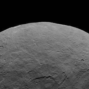 Geology of Ceres - Several long canyons are evident in this view. The large crater that extends off the bottom of the picture is in the center of the picture above. Also notice the bright spots, just visible on the limb at upper left. The first picture above shows them from overhead.