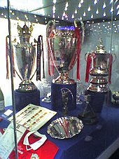 Three silver trophies on blue plinths in a glass display case.