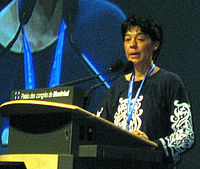 Woman with short dark hair, blue lanyard and black-and-white blouse speaking at a podium