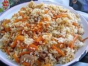 Plat de riz avec des carottes et des morceaux de viande.
