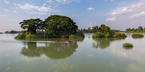 Pirogue and tiny wooded island reflecting in the water