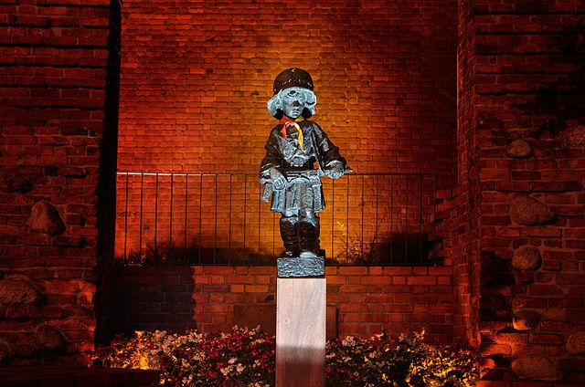 > Statue du petit insurgé de Varsovie de nuit.
