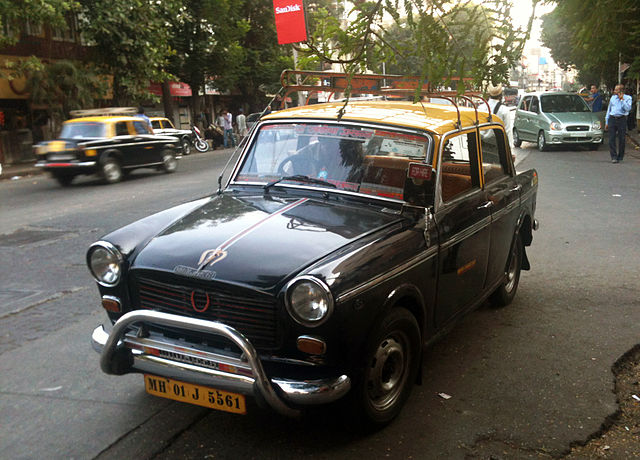 A black and yellow Premier Padmini Taxi on the Streets of Mumbai.