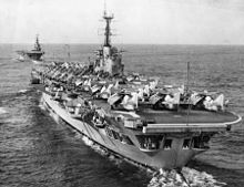 Photograph of an aircraft carrier from behind. Numerous aircraft with their wings folded are sitting on the flight deck. A second aircraft carrier is in the background, leading the first.