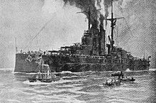 A large battleship sits motionless in the water with smoke coming out of its funnels and three small boats moving beside her in the foreground.