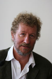 Man with curly brown hair, grey-blue irises, and a short beard. He is wearing a white shirt with the collar open and a jacket.