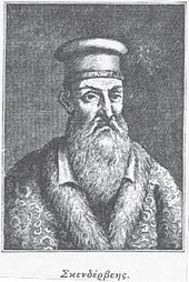 a portrait of a male with a long beard wearing a hat and a fur-collared coat