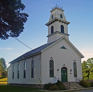 A white church with a rounded steeple and green door
