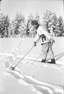 A Finnish soldier on skis, with a fur hat and a tobacco pipe in his mouth, points with a ski pole at the snowy ground, where Soviet soldiers have left tracks. The Finnish troops are in pursuit.