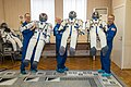 Soyuz MS-08 crew members with their space suits.jpg