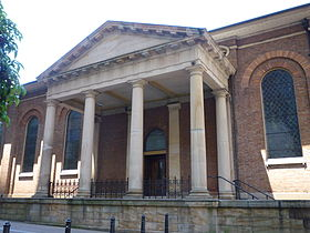 Columns supporting an entablature and pediment extending from the church to create a covered entrance