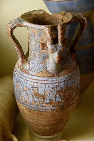 Qift - Storage jar, brown fabric. Blue decorations with lotus flower. Ibex or gazelle's head peeking out from vegetation. 18th Dynasty. From Koptos (Qift), Egypt. The Petrie Museum of Egyptian Archaeology, London