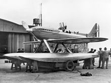 A single-engined monoplane seaplane aircraft is mounted on a wheeled trolley, ten men are standing by the aircraft with one looking into the opened cockpit. The aircraft has 'S1596' painted on the tail.