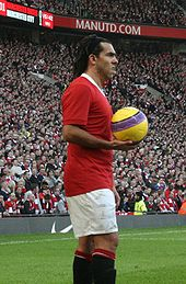 A man wearing a red football shirt, white shorts and black socks. His hair is held back by a hairband. He is holding a yellow football with a purple design.