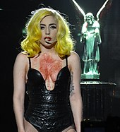 A pale-skinned woman is standing in front of a statue of an angel. She has yellow hair and wears a low-cut garment. Her chest is marked with red liquid.
