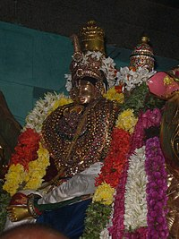 The metal idol of a man decorated with jewellery and flower garlands on whose thigh a woman is seated.