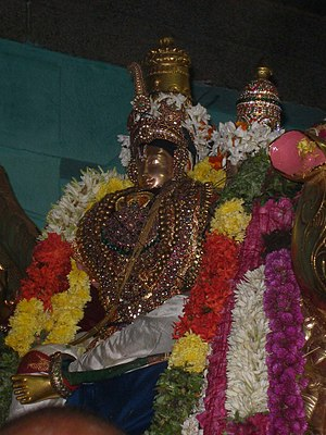 Thirumangai Alvar - Thirumangai Alvar (left) with his wife Kumudavalli (right, only her crown is visible, rest of her image is covered with garlands)