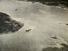 Black and white aerial photograph showing a body of water with a large warship near the shore