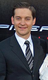 An image of a Caucasian man smiling. He has medium brown hair and is wearing a navy jacket over a white shirt and striped tie.