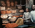 Two merchants sit by their stand of honeycakes in Bombay by Jules Gervais-Courtellemont.jpg