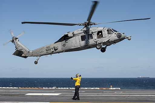 U.S. Navy Aviation Boatswain's Mate (Handling) 1st Class Anthony Morrison directs an MH-60S Seahawk helicopter assigned to Helicopter Sea Combat Squadron (HSC) 7 to land aboard the aircraft carrier USS Harry S 140825-N-NU281-049
