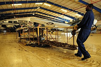 Collections management (museum) - U.S. Navy personnel move a damaged antique plane from the Lone Star Flight Museum during disaster recovery after Hurricane Ike in Galveston, Texas, September 21, 2008.