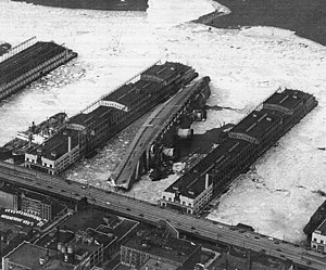 New York Passenger Ship Terminal - The Normandie, renamed USS Lafayette, lies capsized in the frozen mud at Pier 88 in the winter of 1942