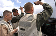 US Navy 030322-N-9964S-013 Landing Signal Officers (LSOs) talk to the pilots during their final approach on the flight deck aboard USS Harry S. Truman (CVN 75)