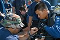 US Navy 030626-N-0493B-008 Operations Specialist 2nd Class Matthew Medeiros, a diver assigned to USS Safeguard (ARS 50) assists Royal Brunei Navy (RBN) diver Cpl. Heidi with preparations for a training dive.jpg