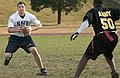 US Navy 051204-N-9851B-005 Cryptologic Technician 3rd Class Cameron Haines, assigned to Seventh Fleet, looks for an open receiver as U.S. Army Sgt. Mark Mullins rushes him at the annual Army vs. Navy flag football game.jpg