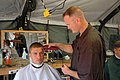 US Navy 060828-N-6652A-029 Ship's Serviceman 2nd Class Heath Wayne gives Electrician's Mate Fireman Nicholas Jacnaos a hair cut during personal time while participating in exercise Seahawk 2006.jpg