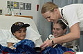 US Navy 061108-N-3750S-174 An eight year-old boy laughs with Hospital Corpsman 2nd Class April Pratt and Ensign Lisa Blachford at the Methodist Children's Hospital.jpg