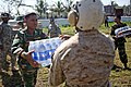 US Navy 071126-M-7696M-153 A U.S. Marine passes a Bangladeshi soldier a case of bottled water while unloading a shipment of food, water, and medical supplies.jpg