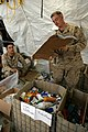 US Navy 081212-M-6159T-206 Religious Program Specialist 2nd Class Charles Swoboda, left, and Religious Program Specialist 3rd Class Jason Shaw organize boxes donated by citizens from across America.jpg