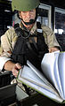 US Navy 090609-N-5345W-155 LT John Fairweather, assigned to Naval Beach Group 2, checks over the ship's bridge logbook while serving as a Visit, Board, Search and Seizure (VBSS) team leader during a VBSS drill.jpg