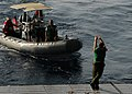 US Navy 090902-N-4680O-074 A Sailor assigned to Helicopter Mine Countermeasures Squadron (HM) 15 throws the spot line to a rigid-hulled inflatable boat.jpg