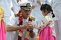 US Navy 110929-N-UN744-219 Capt. David A. Lausman presents a ship's coin to a Korean girl after USS George Washington (CVN 73) arrived in Busan, Re.jpg