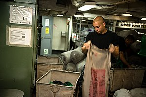 US Navy 120102-N-GC412-007 A Sailor fills a laundry bag with flight deck jerseys.jpg