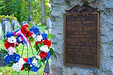 "Close up of a grave stone (on the right) flanked by a red, white, and blue flower wreath (with ribbon and flag) on the left. Among other things, the stone reads ""In Loving Memory of Uncle Sam"""