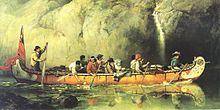 A group of ten plainly-dressed men rowing a canoe beside a large rock face. A furled red flag is in the back of the canoe, and there are blankets beside the men.