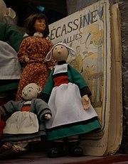 Poupées représentant Bécassine. En arrière plan la couverture d'un album de Bécassine: Bécassine et les Alliés