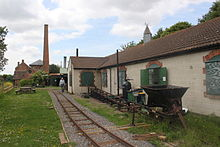 Single storey buildings, with a parallel railway track in front. Between them is a ramp. A chimney can be seen in the distance.