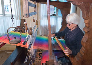 Museum Het Leids Wevershuis - Museum guide and weaver ms Fennema demonstrates the loom. Here she battens the fabric (where the weft is pushed up against the fell of the cloth by the reed). In her left hand the shuttle (which she will propel across the loom in an instant)