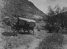 A photograph of a broken down wagon in the African bush country