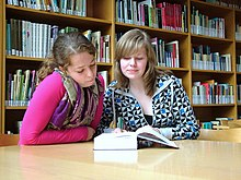 Two teenagers engage in joint attention by reading a book.